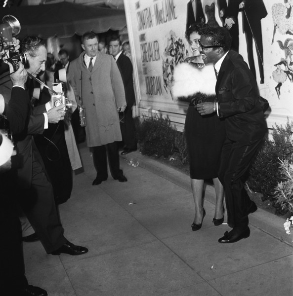 """Sammy Davis Jr. with his sister, Sandy Davis, at the Hollywood premiere of """"Can-Can"""" posing for photographers, including Nat Dillinger, who is leaning forward1960© 1978 Sid Avery - Image 0009_0003"""