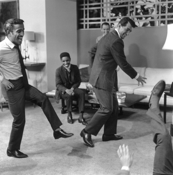 """Sammy Davis Jr. and Dean Martin staging a fight with Joey Bishop on the ground and Frank Sinatra watching in the background on the set of """"Ocean"""