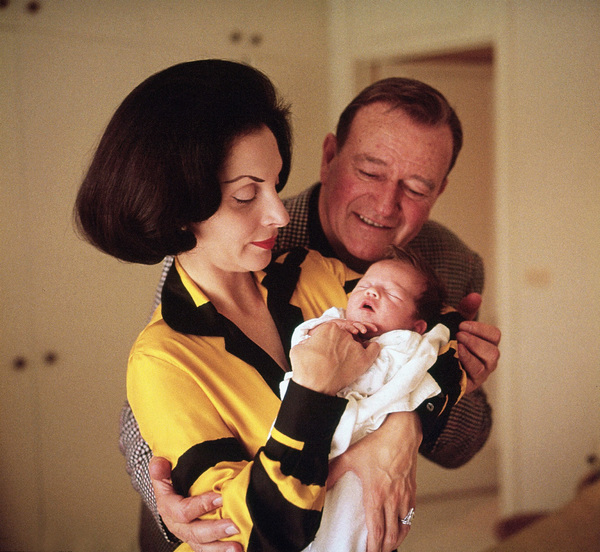 John Wayne at home with his wife Pilar and their new baby Marisa 1966 © 1978 Bernie Abramson - Image 0898_3271