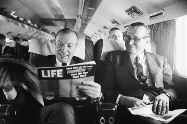 Photographer Mark Shaw on a plane reading a November 10, 1961 issue of Life magazine with Dr. Max Jacobson looking on © 2012 Mark Shaw - Image 17397_0006