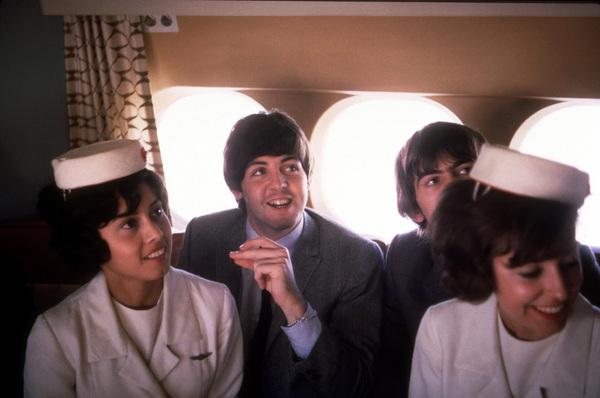 The Beatles, (Paul McCartney, George Harrison) on the plane with flight attendants, 1964 © 1978 Gunther / MPTV - Image 7685_0044